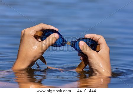 hand of smimmer holding swimming goggles on water background