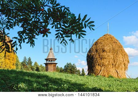 haystack on the background of a wooden church in Russia