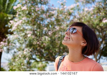 Young smiling beautiful woman standing near flower tree with reflection of palm trees in sunglasses. Summer vacation. Travelling