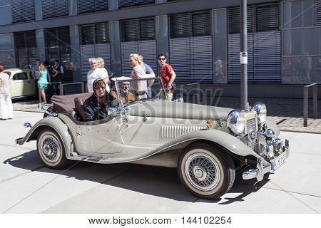 COLOGNE GERMANY - AUG 7 2016: Elderly couple in a historic Mercedes Benz roadster in the city of Cologne Germany