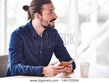 Young trendy caucasian man with long hair tied in a bun, looking off camera while holding a phone in his hands with a coffee on the table in front of him and copy space to the right of him.