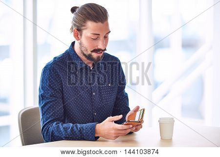 Trendy handsome man with long hair tied back in a bun busy using his mobile phone to stay connected while sitting at restaurant table.