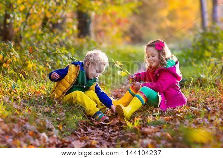Happy children playing in beautiful autumn park on cold sunny fall day. Kids in warm jackets play with golden leaves.