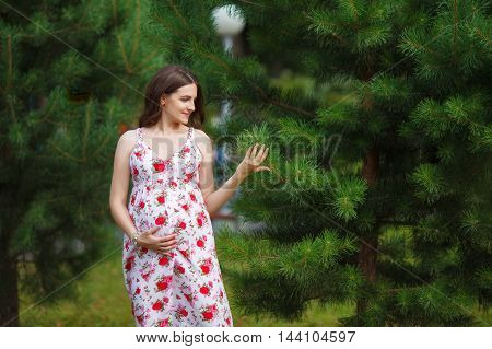 Young pregnant woman touching her belly with hands