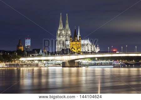 Cologne Cathedral and the Great Saint Martin Church in Cologne illuminated at night. North Rhine-Westphalia Germany