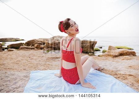 Close up portrait of a happy cheerful pin up girl in red swimsuit winking while sitting on the beach