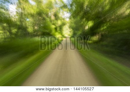 An abstract view from a bicycle speeding down a bike trail.