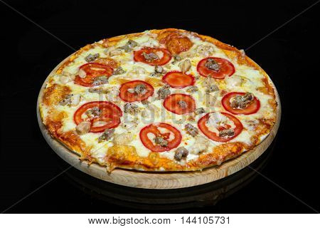 Italian pizza with chicken meat pork veal on a black background