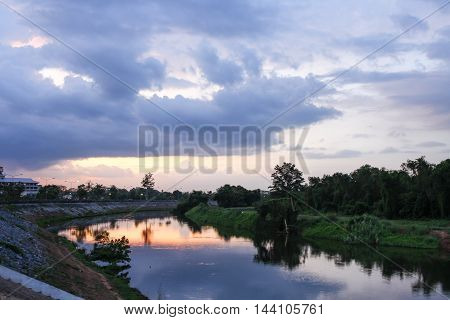 Colorful sky and colorful water in lake reflected in evening time after sunset Select focus with shallow depth of field Soft focus due long exposure : ideal use for background .