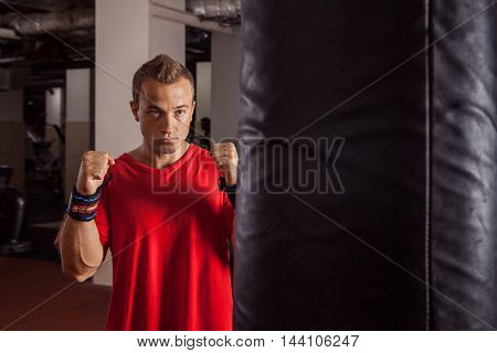 Muscular boxer is striking the boxing bag.