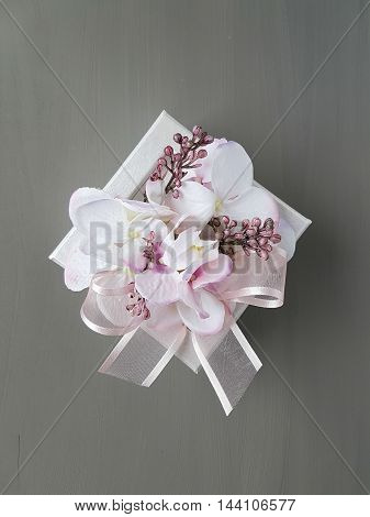 white wrapped gift box with flowers and bow