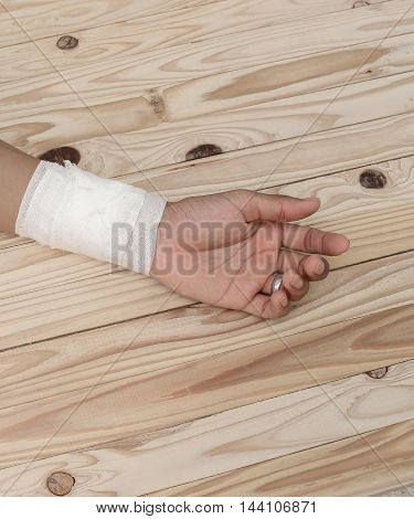 Gauze bandage the hand contusion. treating patients with hand with a wrist left male With gauze wrapping his injury On a wooden table