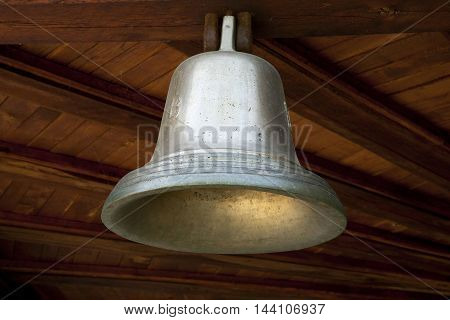 little shiny bell hanging on wooden ceiling