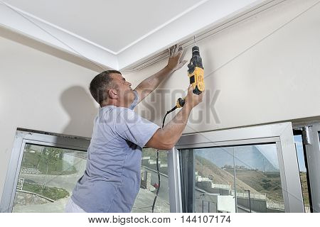 Worker Drilling Hole at Ceiling