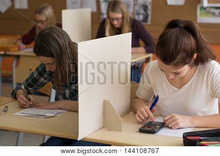 Teenager makes in the class a test - situation with four girls
