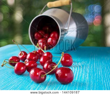 Cherry fruit. Sprinkled cherry on a blue wooden table.