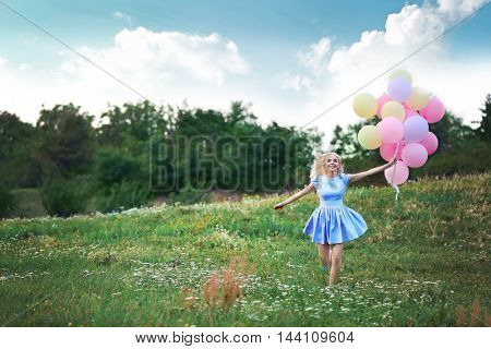 Beautiful young woman holding air balloons in field