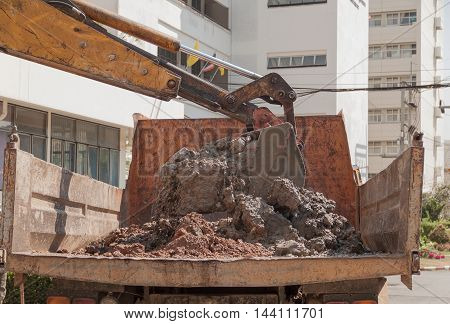 Excavator or soil mud into truck body Work in day with sunlight.