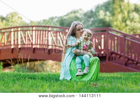 mom hugs small daughter in Park background of trees