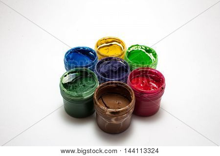 a set of seven pots of paint on a white background