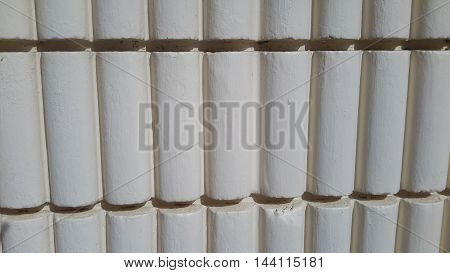 white half-cylinder rows embedded in decorative concrete wall siding, Songkhla, Thailand