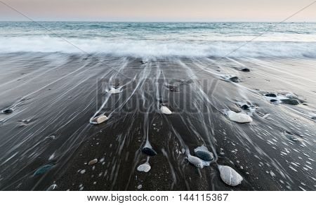 Pebbles on the beach on black sand and flowing sea water from waves creating nice textures. Long exposure image.