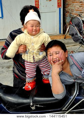 Pengzhou China - February 25 2011: Woman holding her grandson with a smiling older Chinese boy on their Sichuan family farm
