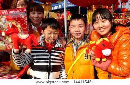 Pengzhou China - January 31 2014: Smiling vendors selling Year of the Horse decorations and toys for the Chinese New Year holiday in Long Xing Square