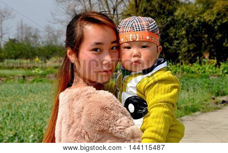 Pengzhou China - March 14 2014: Young Chinese mother holding her baby son on the family's Sichuan province farm