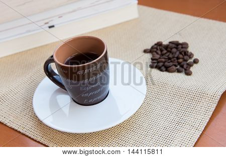 Cup of aromatic espresso black coffee and roasted beans