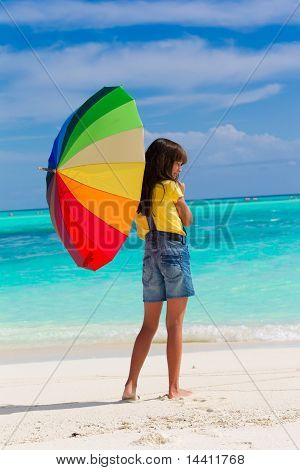Girl on beach with umbrella