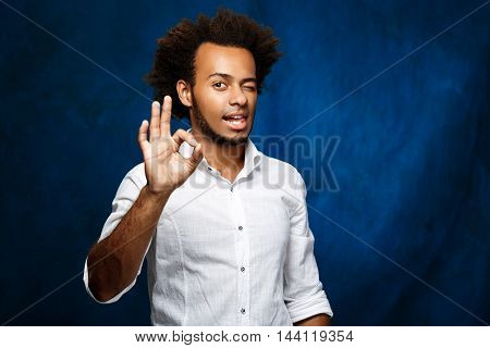 Young handsome african man in white shirt showing okay, winking over blue background. Copy space.