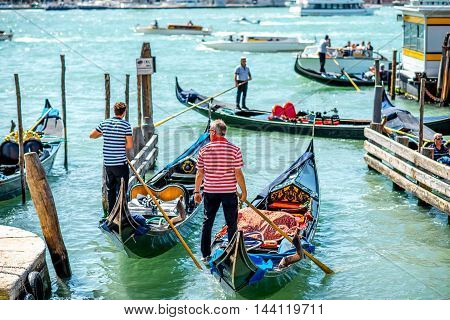 Venice, Italy - May 18, 2016: Gondoliers sail on gondolas full of tourists in water canal in Venice. Gondola is a traditional venetian boat and famous tourist attraction.