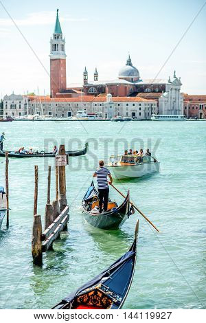 Venice, Italy - May 18, 2016: Gondoliers sail on gondolas full of tourists with San Georgio Maggiore island on the background in Venice.