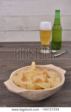 Gold salted potato chips in a wooden bowl on a rustic brown table with a beer glass and a bottle in the background