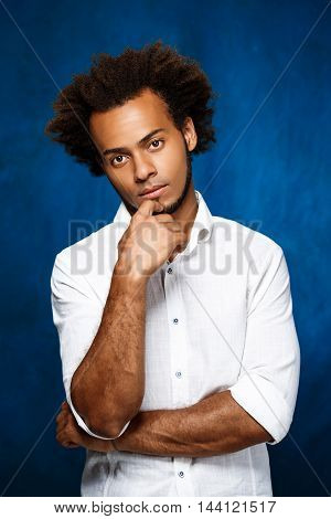 Portrait of young handsome african man in white shirt looking at camera over blue background. Copy space.