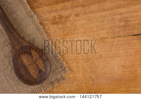 Serving spoons on burlap cloth on wooden surface image brown tone