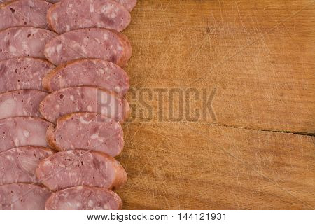 sliced sausages on wood chopping board. Top view.