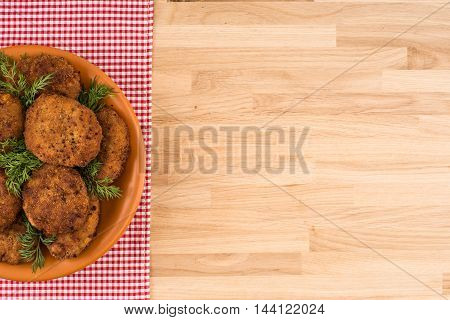 Fried cutlet in the plate on wooden table
