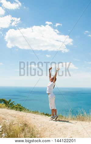 girl standing on a mountain overlooking the sea and sky with clouds in summer