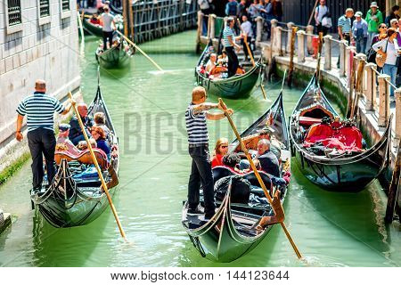 Venice, Italy - May 18, 2016: Gondoliers sail on gondolas full of tourists in the narrow water canal in Venice. Gondola is a traditional venetian boat and a famous tourist attraction.