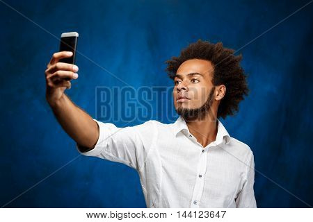 Young handsome african man in white shirt making selfie over blue background. Copy space.