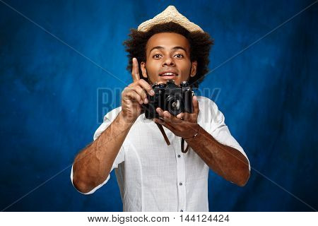 Young handsome african man in white shirt and hat holding old camera, posing over blue background. Copy space.