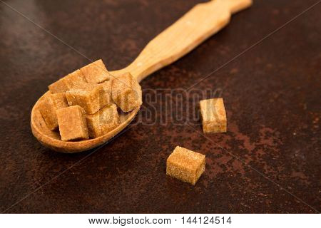 brown Sugar cubes on the wooden spoon.
