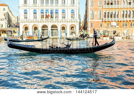 Venice, Italy - May 18, 2016: Gondolier sail with tourists in gondola in Grand canal in Venice. Gondola is a traditional venetian boat and a famous tourist attraction.