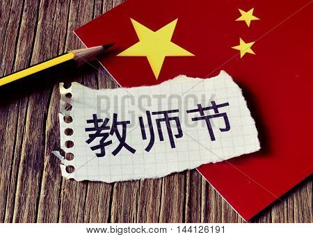 closeup of a piece of paper with the text Teachers Day written in Chinese, a pencil and the flag of China, placed on a rustic wooden surface