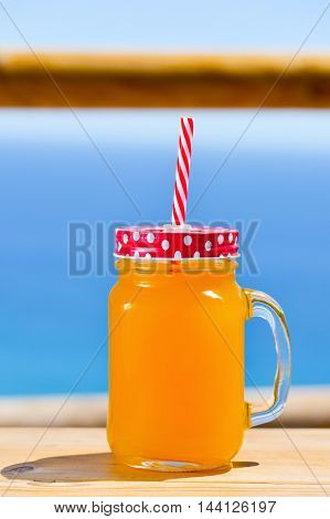 closeup of an orange beverage served in a glass mason jar with a red lid patterned with white dots, and a red and white drawing straw, and the ocean in the background