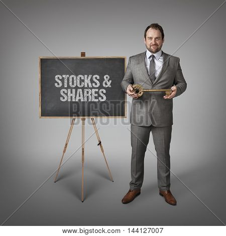 Stocks and Shares text on  blackboard with businessman and key