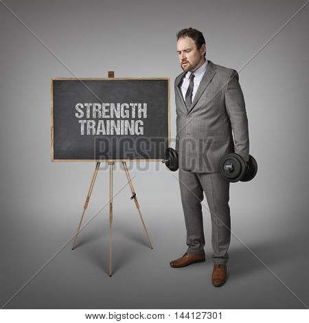 Strength training text on blackboard with businesssman holding weights