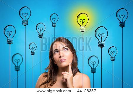 Portrait happy young woman thinking dreaming has many ideas looking up isolated blue wall background. Positive human face expression emotion feeling life perception.